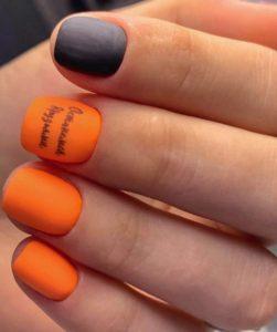 Матовый оранжевый маникюр с надписью на коротких ногтях